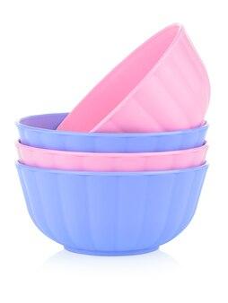 白い背景の上のさまざまな色の子供のプラスチック製食器のセットです。