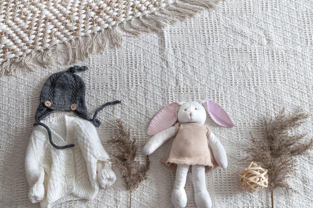 Набор детской стильной вязанной одежды ручной работы с различными аксессуарами в стиле бохо, вид сверху.