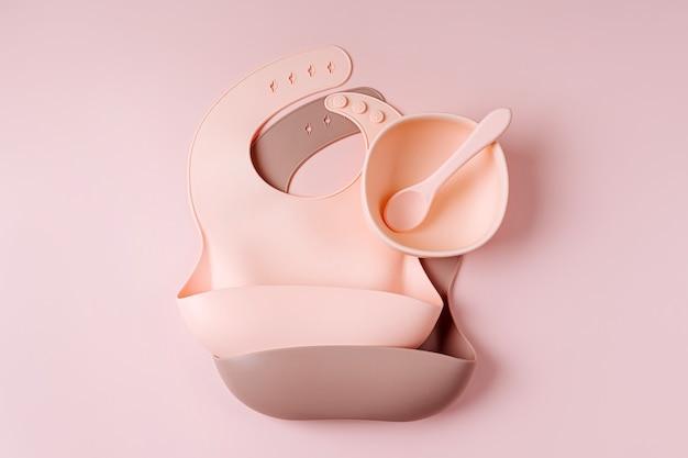 어린이용 식기와 실리콘 턱받이 세트. 아기 액세서리. 영양 및 수유 개념입니다. 평면도, 평면도
