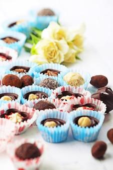 明るい木製の背景に花とチョコレート菓子のセット、クローズアップ