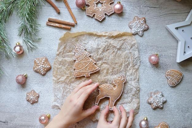 新年の装飾が施されたテーブルの上のクリスマスジンジャーブレッドヘリンボーンと鹿のセット。クリスマスのベーキングの概念。