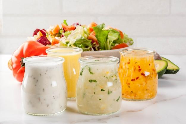 ハニーマスタード、牧場、ビネグレット、レモン&オリーブオイルの古典的なサラダドレッシングのセット、白い大理石のテーブルの上、