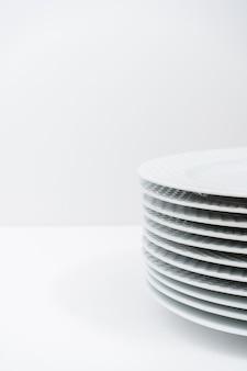 白いテーブルの上にきれいに積み重ねられた白いプレートのセット。コピースペース