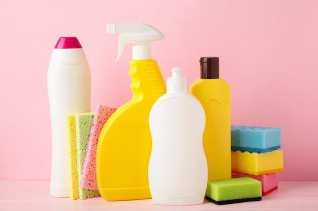 Набор чистящих инструментов на розовом фоне.