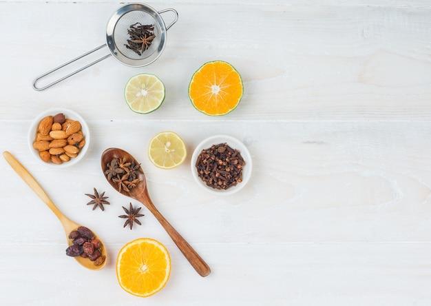 白い表面の白いボウルにクローブと柑橘系の果物とアーモンドのセット