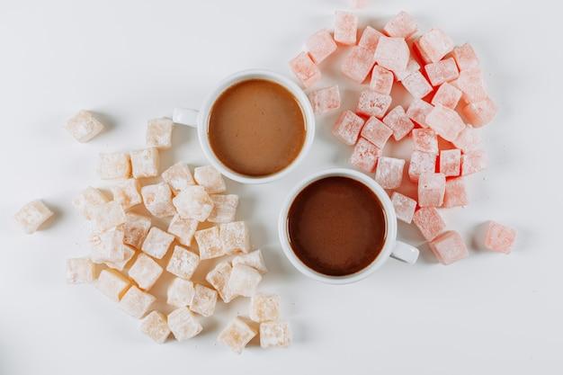 Набор кофе и лукум лукум в мисках на белом фоне. вид сверху.