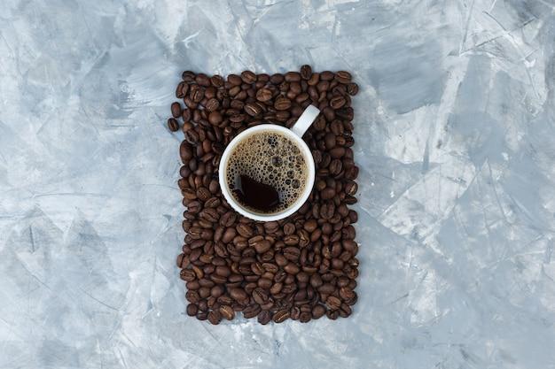 青い大理石の背景のカップにコーヒー豆とコーヒーのセットです。上面図。