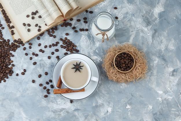 Набор кофейных зерен, книги, молока, специй и кофе в чашке на сером фоне гипса. вид сверху.