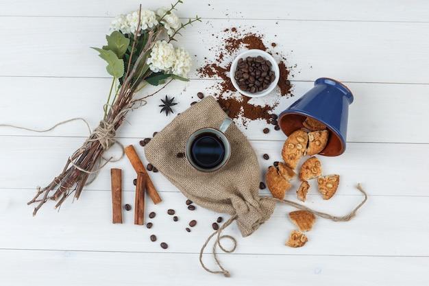 コーヒー豆、クッキー、花、シナモンスティック、コーヒーのセットは、木製と袋の背景にカップで。上面図。