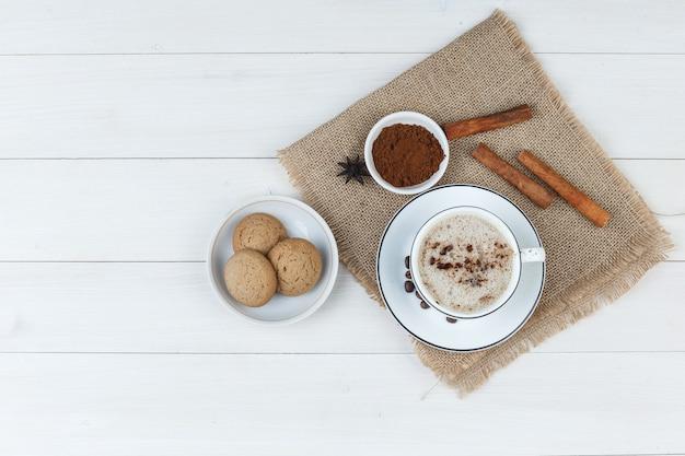 Набор кофейных зерен, молотого кофе, специй, печенья и кофе в чашке на деревянном фоне и кусок мешка. вид сверху.