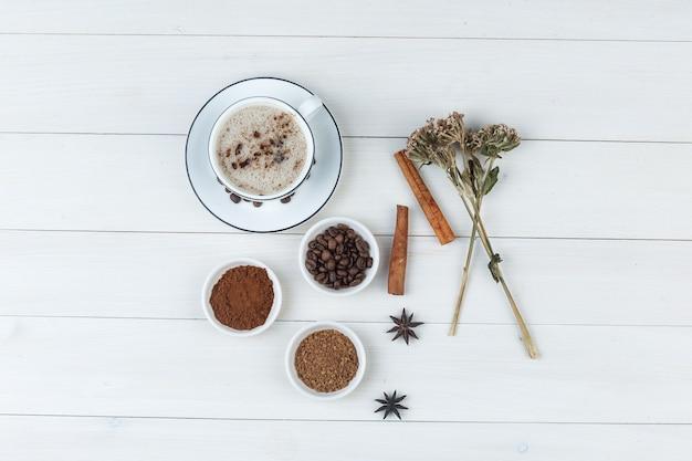 커피 콩, grinded 커피, 향신료, 쿠키, 말린 된 허브와 나무 배경에 컵에 커피의 집합입니다. 평면도.