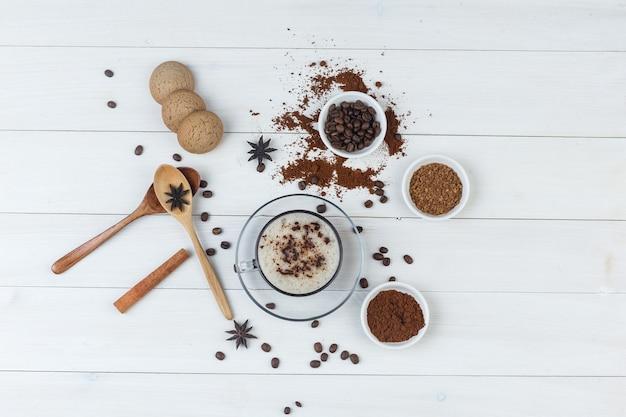 コーヒー豆、挽いたコーヒー、スパイス、クッキー、木のスプーン、木製の背景の上のカップのコーヒーのセットです。上面図。