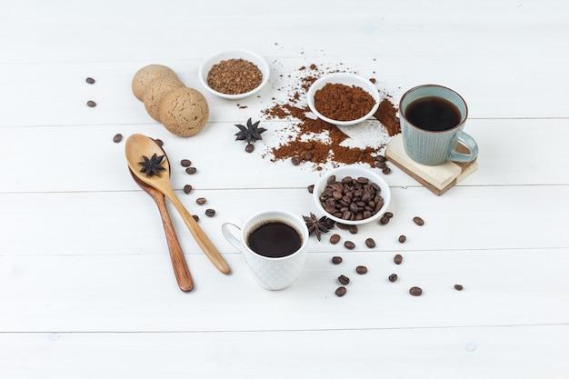 コーヒー豆、挽いたコーヒー、スパイス、クッキー、木のスプーン、木製の背景の上のカップのコーヒーのセットです。ハイアングルビュー。