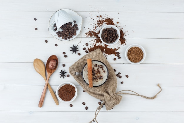 コーヒー豆、挽いたコーヒー、スパイス、木のスプーン、木製と袋の背景にカップのコーヒーのセットです。上面図。