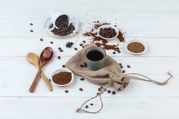 コーヒー豆、挽いたコーヒー、木のスプーン、木製と袋の背景にカップのコーヒーのセットです。ハイアングルビュー。