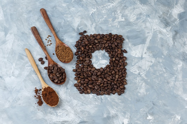 커피 콩, 인스턴트 커피, 나무 숟가락에 커피 가루와 밝은 파란색 대리석 배경에 커피 콩의 집합입니다. 확대.