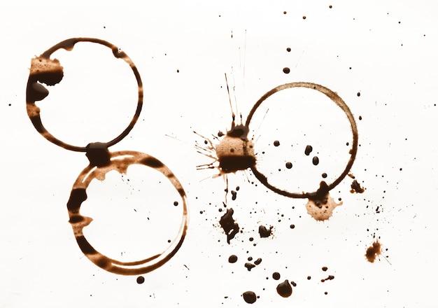 白い背景で隔離のコーヒーカップの汚れのセット。乾いた指輪とブレーシング飲料のしぶき。グランジデザインの茶色の斑点のコレクション