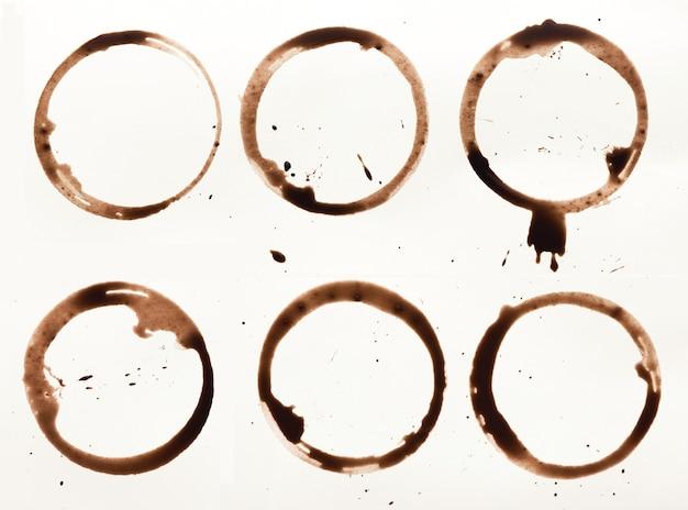 白い背景で隔離のコーヒーカップの汚れのセット。ブレーシング飲料のドライリング。グランジデザインの茶色の斑点のコレクション