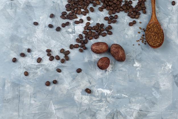 木のスプーンとコーヒー豆、水色の大理石の背景にクッキーのコーヒー粉のセット。上面図。