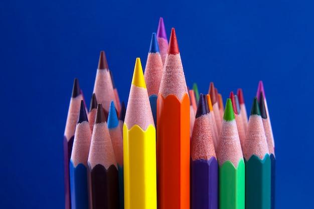 Набор цветных карандашей на ярко-синем. инструменты для рисования. палитра творчества
