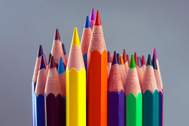 Набор цветных карандашей на сером пространстве. инструменты для рисования. палитра в творчестве