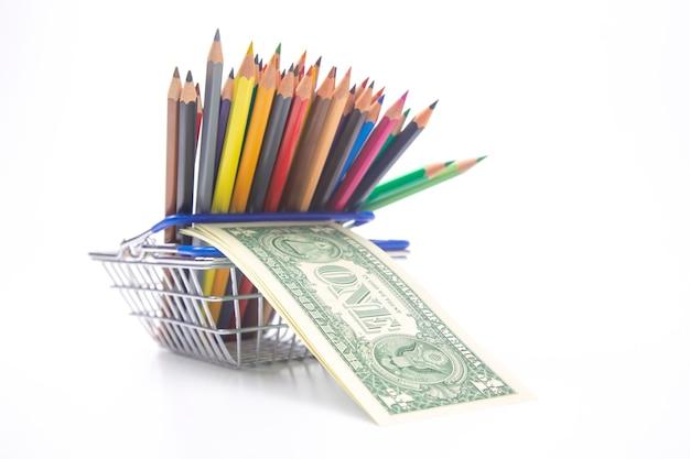 Набор цветных карандашей для рисования в корзине с долларовой банкнотой. продажи и маркетинг