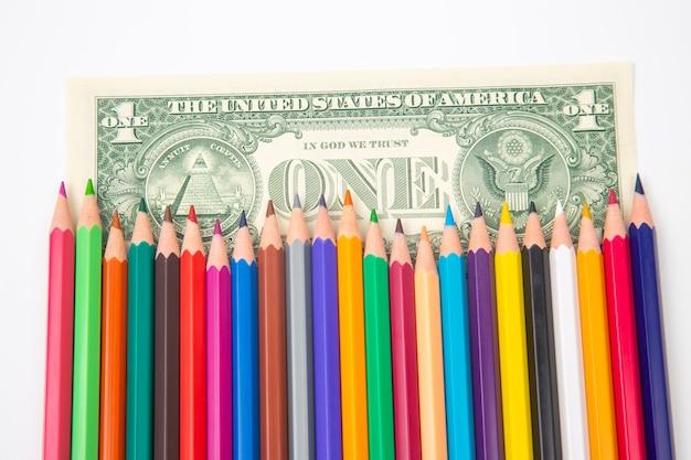 Набор цветных карандашей для рисования на долларовом фоне. продажи и маркетинг
