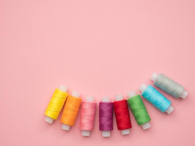 コピースペースとピンクの背景に裁縫用の色のスレッドのセット。