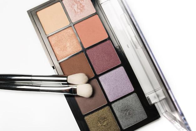 Набор красочных косметических палитр теней для век с кистями для макияжа, изолированные на белом фоне