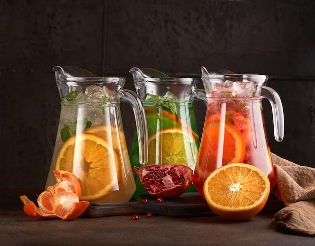 주전자, 빨간색, 노란색 및 녹색의 다채로운 레모네이드 세트. 어두운 배경에. 공간, 선택적 초점을 복사합니다. 건강한 음식. 메뉴 사진