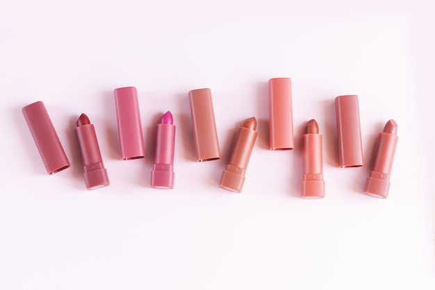 淡いピンクの背景にカラフルな口紅のセット。フラットレイ、上面図