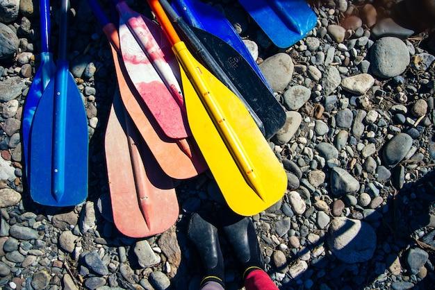 다채로운 노 세트와 해변 바위에 카약과 카누의 패들