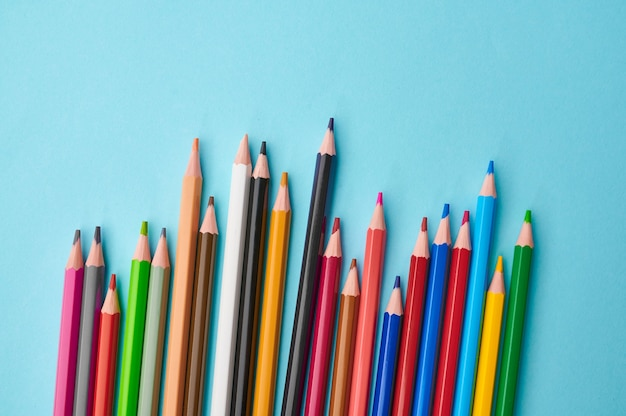 Набор красочных карандашей крупным планом, синий фон. канцелярские товары, школьные или образовательные принадлежности, инструменты для письма и рисования