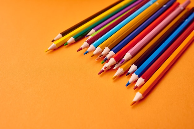 Набор красочных карандашей крупным планом, оранжевая стена. канцелярские товары, школьные или образовательные принадлежности, инструменты для письма и рисования