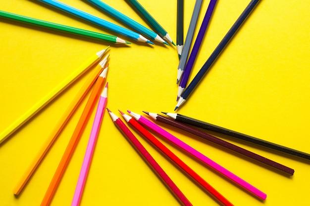 노란색 배경에 다채로운 연필 세트는 사각형 모양의 원으로 배치됩니다. 학교로 돌아가다