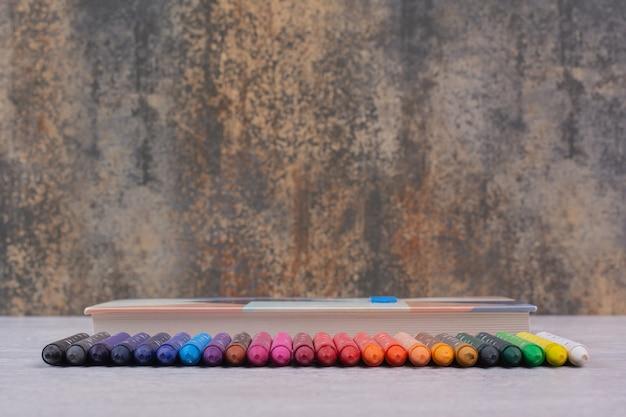 Набор красочных карандашей на белом столе.