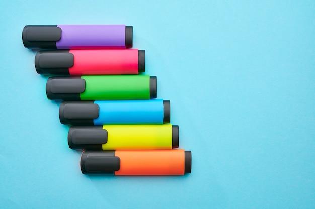 青い背景にカラフルな油性マーカーのセット。オフィスの文房具、学校や教育の付属品、書き込みおよび描画ツール