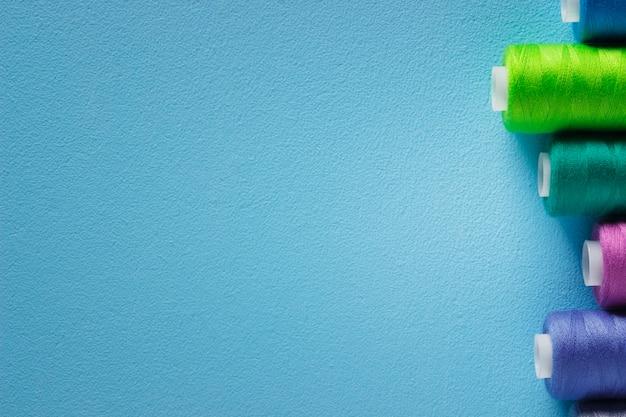 青い背景のスレッドのカラフルなスプールのセットです。