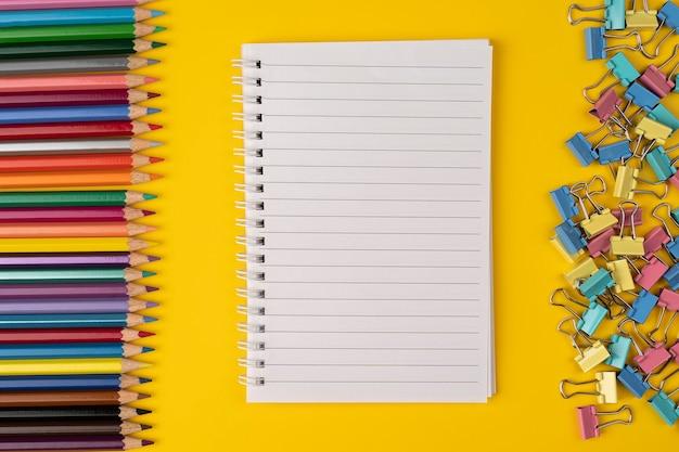 Набор красочных принадлежностей белый пустой блокнот с цветными карандашами на желтом фоне вид сверху