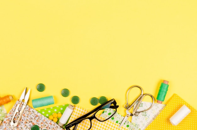 カラフルな黄色と緑の生地、はさみ、ボタン、糸とグラスのスプールのセット