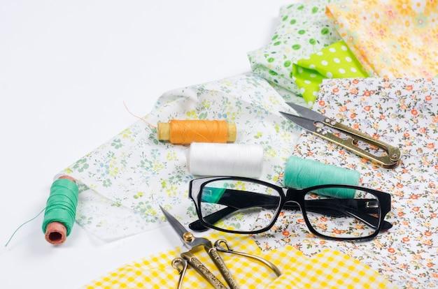 화려한 노란색과 녹색 직물, 가위, 단추, 실과 안경의 스풀 세트