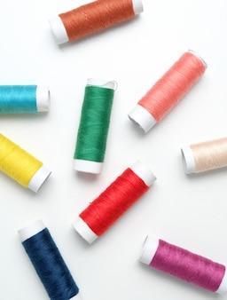 흰색 바탕에 바느질에 대 한 색상 스레드의 집합입니다.