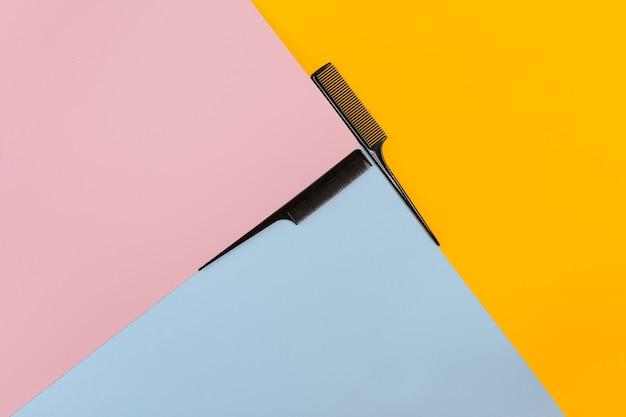 색상 분홍색, 노란색, 파란색 종이 배경에 빗 세트. 평면도. 공간을 복사합니다. 정물. 모형. 플랫 레이