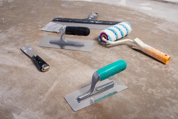 건설 도구, 장식용 석고 나이프, 페인트 롤러, 콘크리트 바닥에 건설 모형 세트