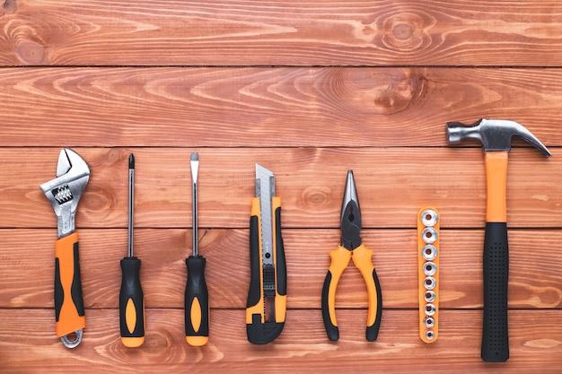 Набор строительных инструментов на фоне коричневого дерева. молоток, гаечный ключ, плоскогубцы и отвертка. рамка-бордюр, открытка к празднику день труда. оборудование, рабочее место. плоский дизайн, копия пространства.
