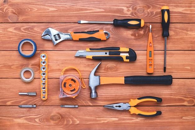 갈색 나무 바탕에 건설 도구 세트입니다. 망치, 렌치, 펜치 및 드라이버. 휴일 노동절을 위한 기프트 카드. 장비, 직장. diy 개념입니다. 플랫 레이. 오버 헤드보기.