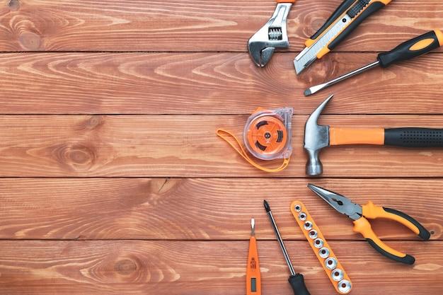 나무 배경에 건설 도구 세트입니다. 망치, 렌치, 펜치 및 드라이버. 휴일 노동절, 아버지의 날 프레임. 장비, 직장. 평평한 위치, 텍스트 복사 공간.