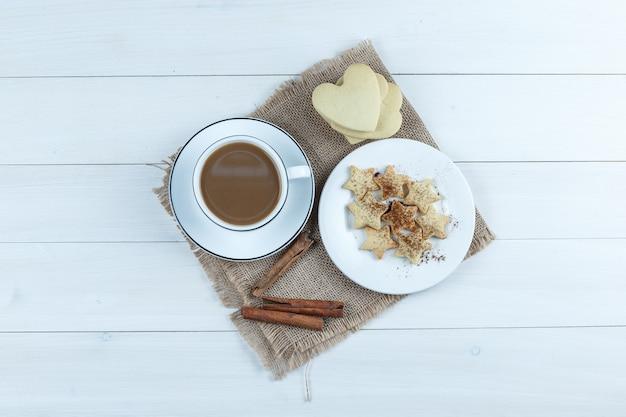 Набор печенья, палочек корицы и кофе в чашке на фоне деревянных и кусок мешка. вид сверху.
