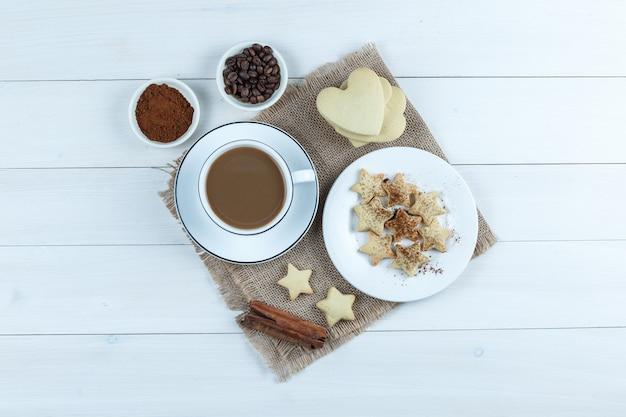 Набор печенья, палочек корицы, кофейных зерен, молотого кофе и кофе в чашке на деревянном фоне и кусок мешка. вид сверху.