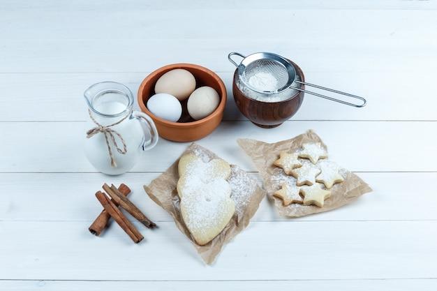 쿠키, 계피 스틱, 우유, 설탕 가루 및 나무 배경에 그릇에 계란의 집합입니다. 높은 각도보기.